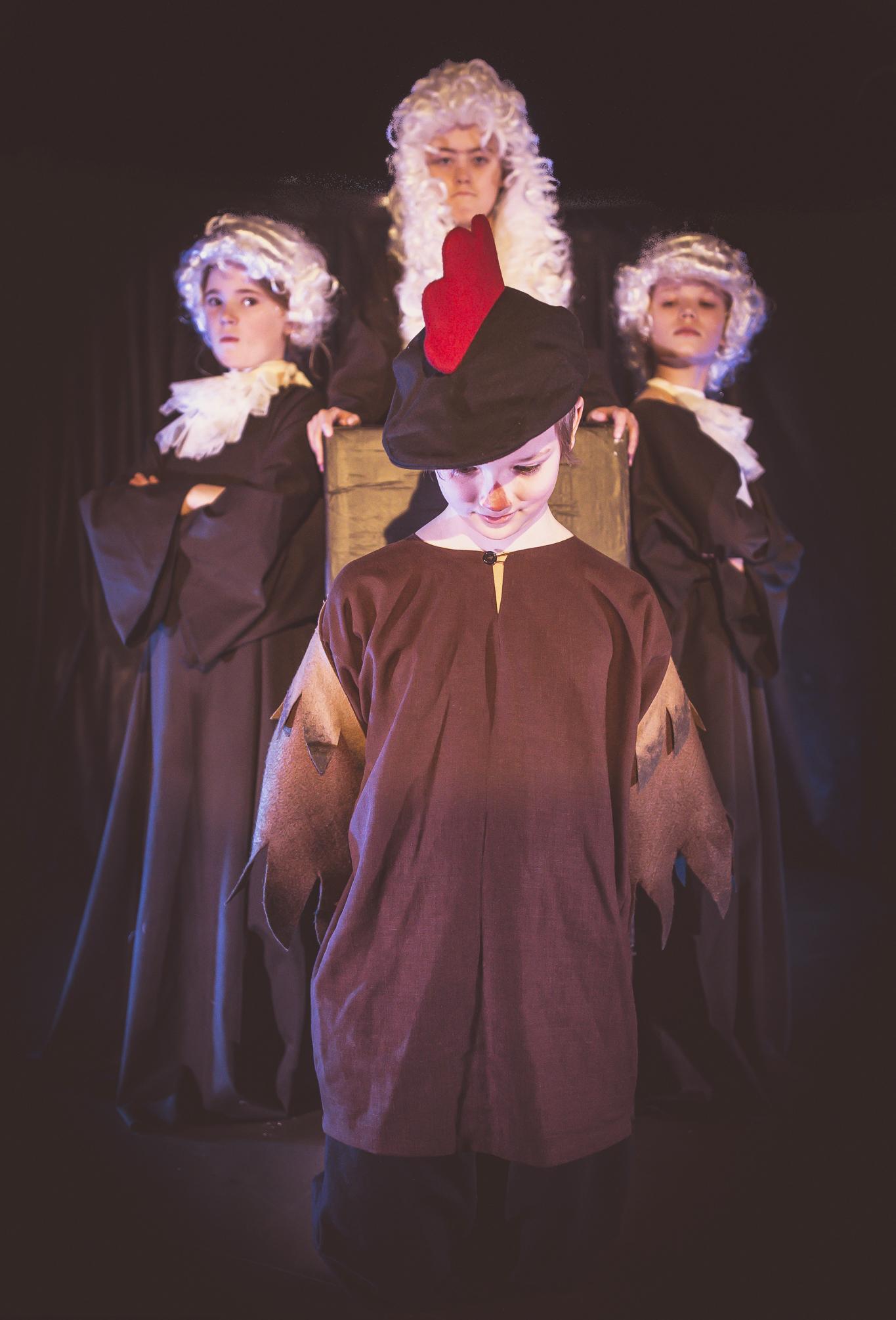 Takana vas. Puolustusasianajaja (Alisa Vahala), Tuomari (Ronja Raittio), syyttäjä (Ella Lehtinen), edessä: Kukko (Gabriel Lillberg)